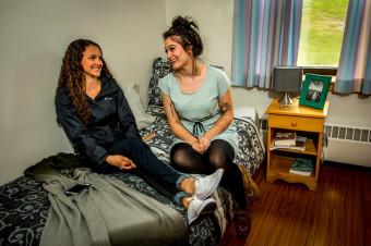 Des jeunes filles assises sur un lit de résidence