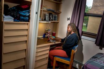 Une étudiante travaille à son bureau en résidence