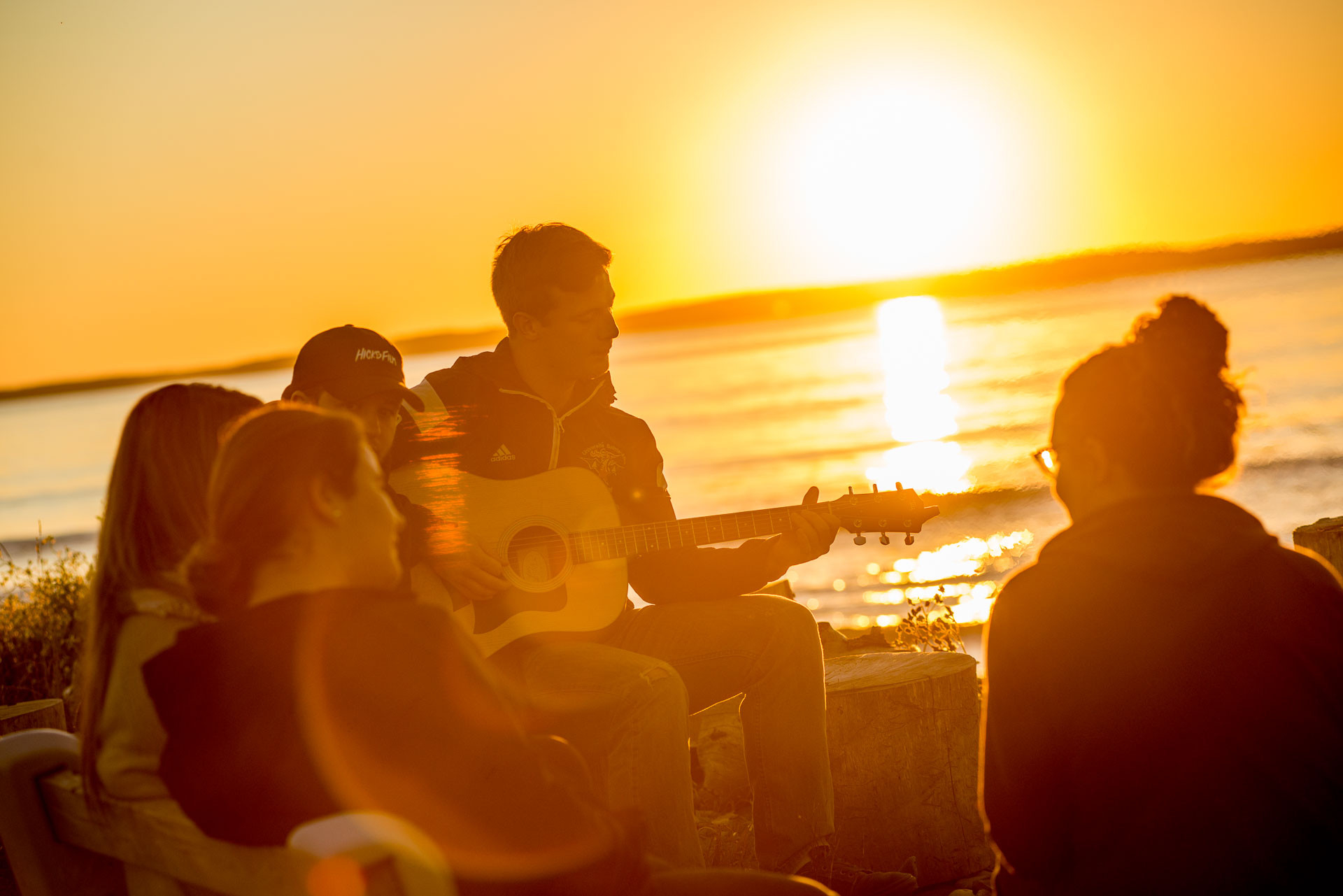 Des étudiants apprécient les feux de camp au coucher du soleil le long de la côte de la baie Sainte-Marie.